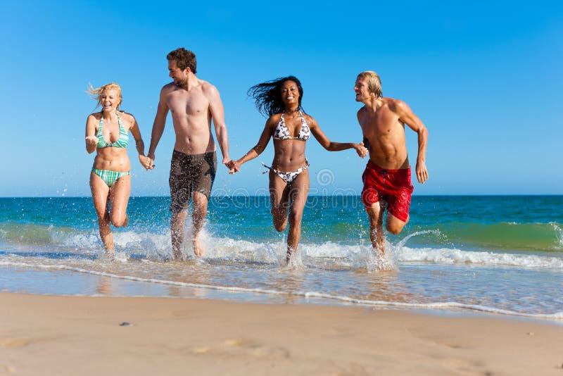 Amigos que se ejecutan el vacaciones de la playa imagen de archivo