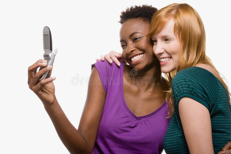 Amigos que se fotografían con el teléfono celular imagen de archivo