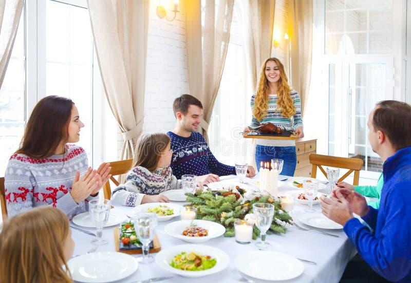 Amigos que se sientan alrededor de una tabla y que gozan del tog de la cena de la Navidad imagen de archivo