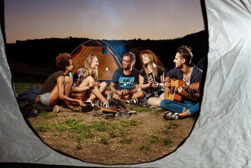 Amigos que se sientan cerca de la hoguera, sonrisa, tocando la guitarra Melcocha de la parrilla que acampa imágenes de archivo libres de regalías