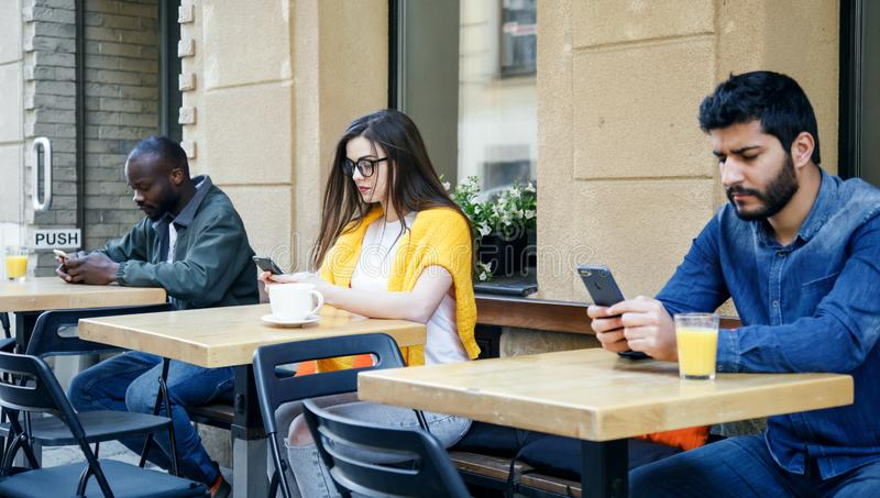 Amigos que se sientan con smartphones foto de archivo libre de regalías