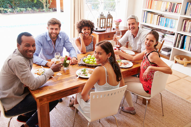 Amigos que se sientan en una mesa de comedor que mira la for Comedor que se extiende