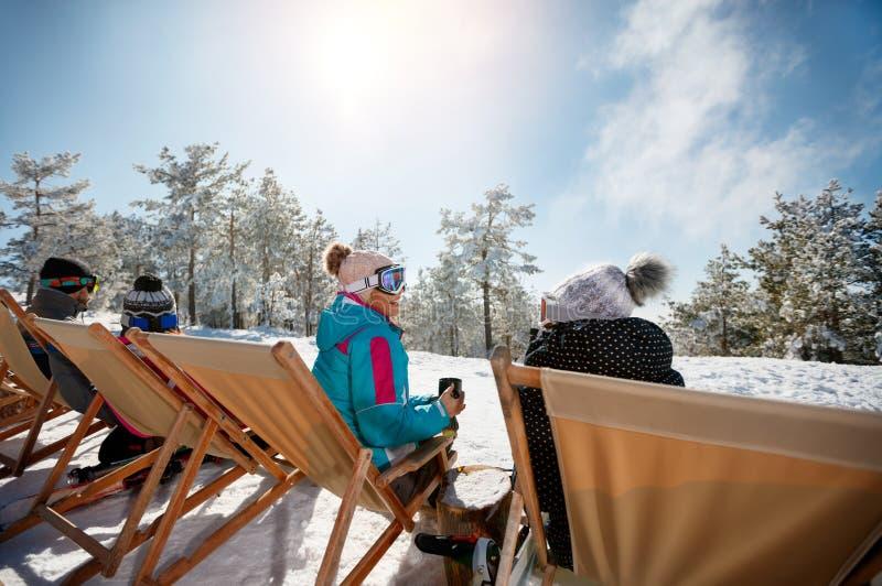 Amigos que sentam-se com as cadeiras de plataforma em montanhas do inverno Vista traseira imagens de stock