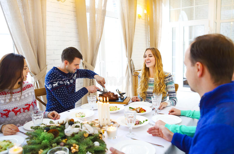 Amigos que sentam-se em torno de uma tabela e que apreciam o tog do jantar de Natal foto de stock royalty free