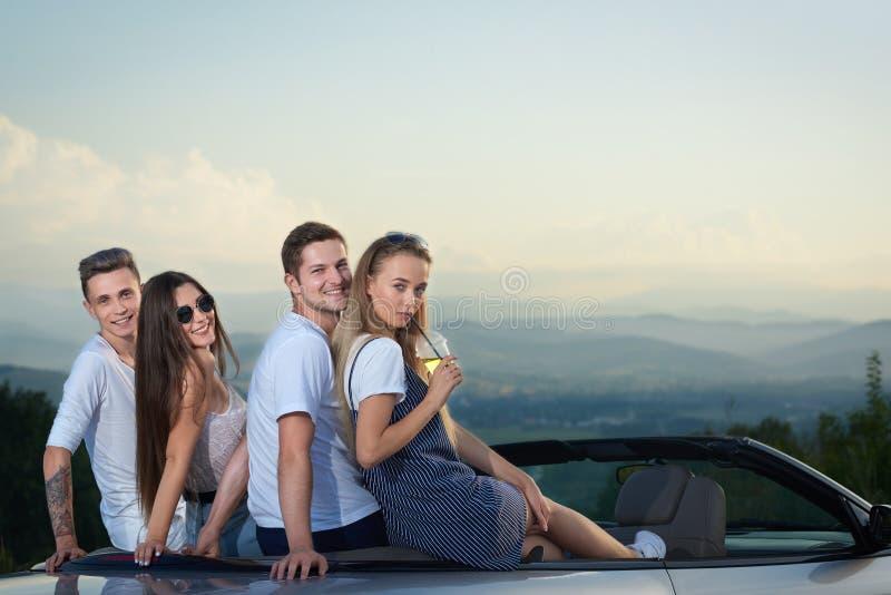 Amigos que sentam-se no cabriolet e que olham para trás na câmera fotografia de stock royalty free