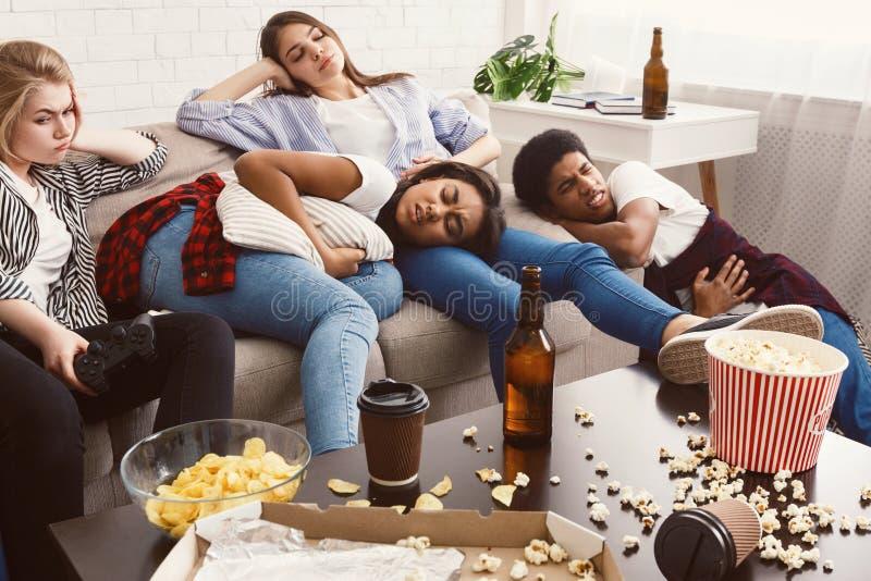 Amigos que sofrem da dor de estômago e da dor de cabeça na sala desarrumado imagem de stock
