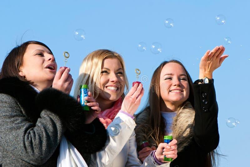 Amigos que soplan burbujas en la naturaleza foto de archivo