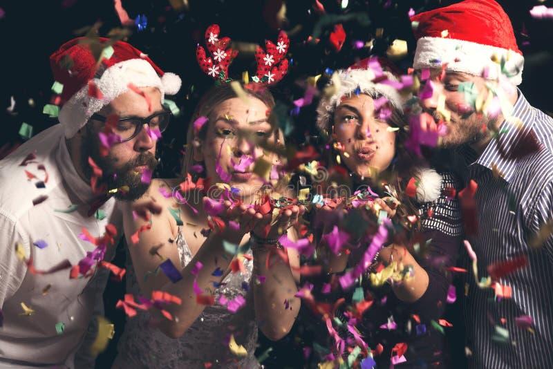 Amigos que soplan confeti colorido ausente fotos de archivo