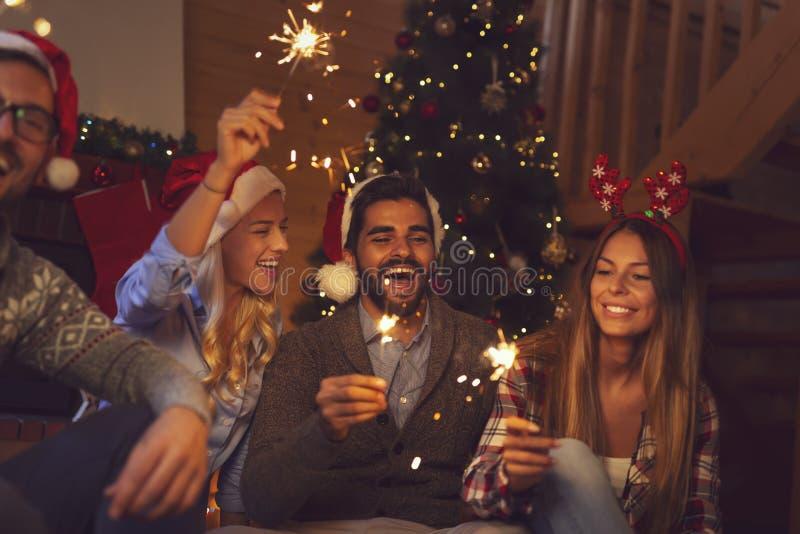 Amigos que sostienen bengalas en la medianoche del ` s Eve del Año Nuevo fotografía de archivo libre de regalías
