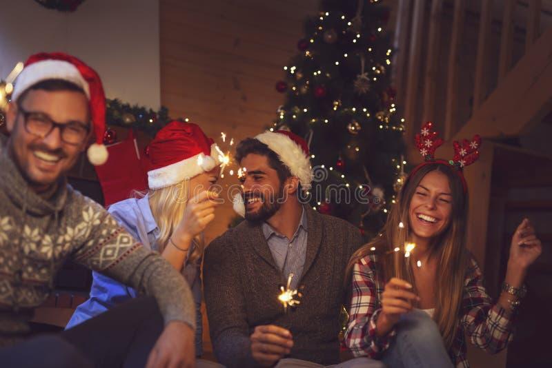 Amigos que sostienen bengalas en Nochevieja a la medianoche imagen de archivo libre de regalías