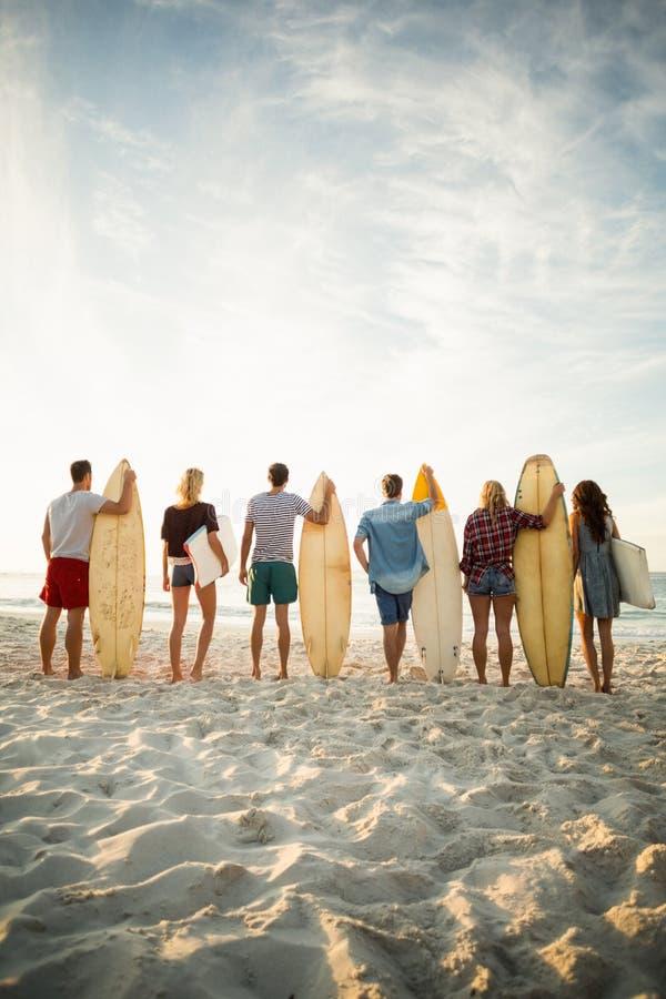 Amigos que sostienen la tabla hawaiana en la playa fotografía de archivo