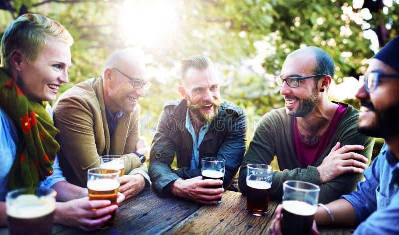 Amigos que têm a diversidade das cervejas exterior foto de stock
