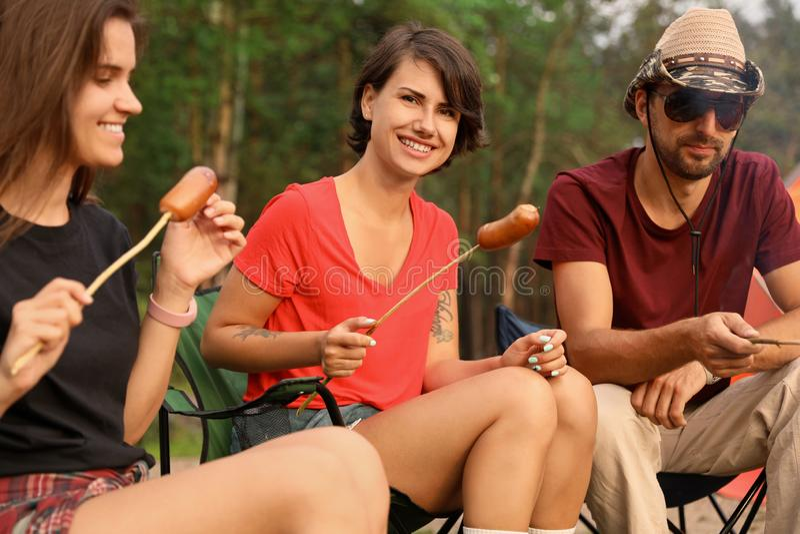 Amigos que têm o almoço com salsichas imagens de stock royalty free