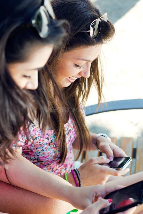Amigos que têm o divertimento com smartphones