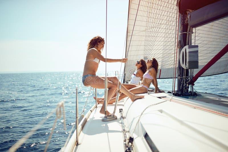 Amigos que têm o divertimento em um barco e que apreciam em férias do cruzeiro imagens de stock royalty free