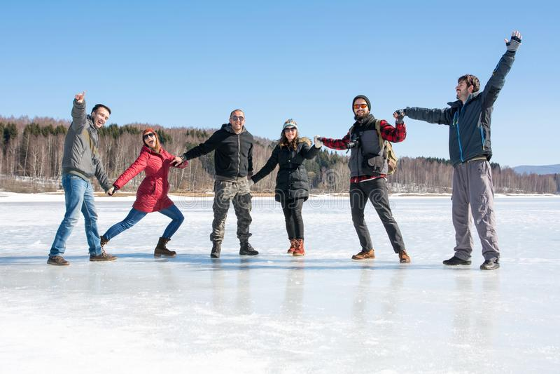 Amigos que têm o divertimento em um lago congelado fotos de stock royalty free