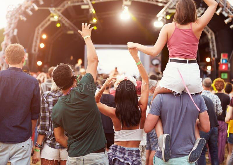 Amigos que têm o divertimento na multidão no festival de música, vista traseira imagens de stock