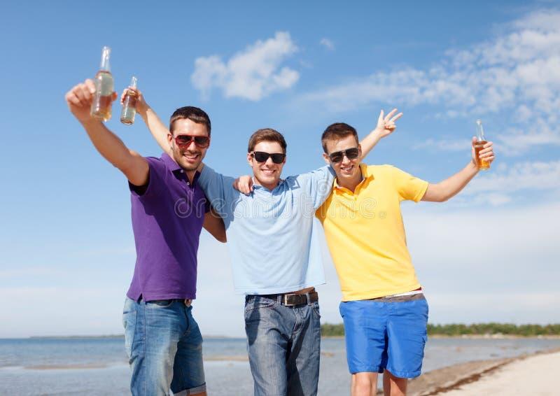 Amigos que têm o divertimento na praia com as garrafas da cerveja imagem de stock royalty free