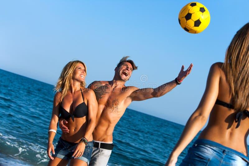 Amigos que têm o divertimento na praia com esfera. imagens de stock royalty free