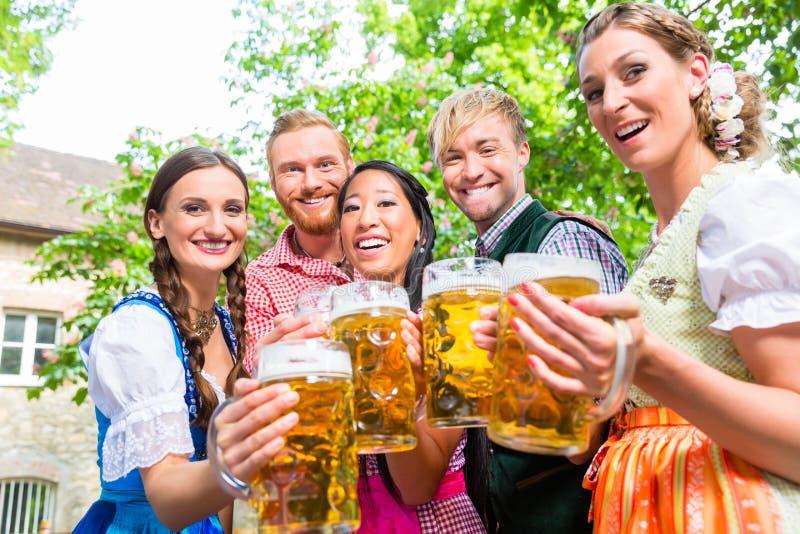 Amigos que têm o divertimento no jardim da cerveja quando vidros do tinido imagens de stock