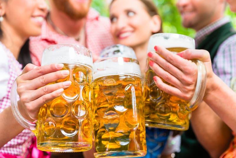 Amigos que têm o divertimento no jardim da cerveja quando vidros do tinido fotos de stock