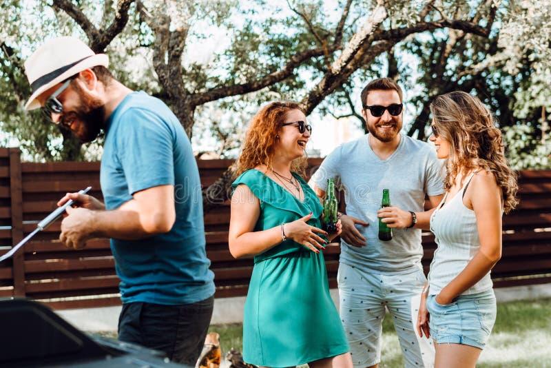 Amigos que têm um partido do assado e meninas que riem e que bebem cervejas claras em um dia de verão quente fotos de stock