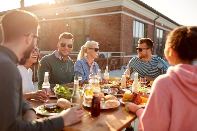 Amigos que t?m o jantar ou o partido do BBQ no telhado fotografia de stock royalty free
