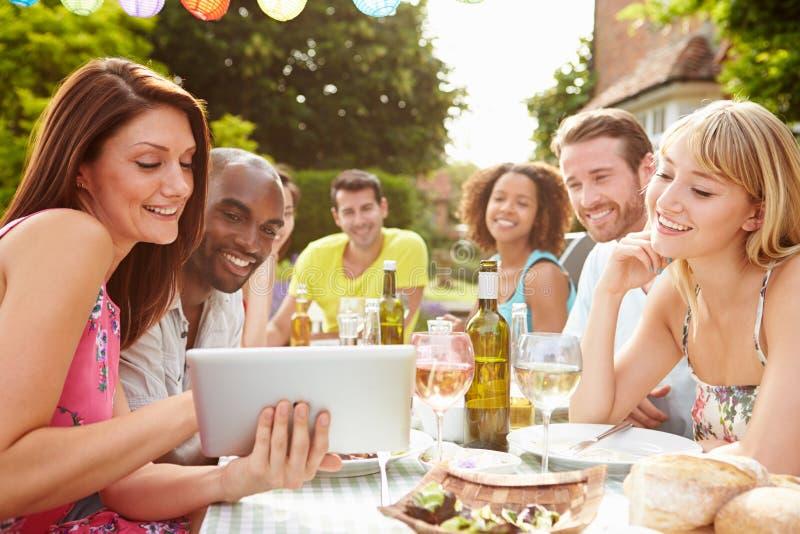 Amigos que tienen barbacoa en casa que mira la tableta de Digitaces imagen de archivo