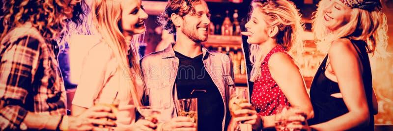 Amigos que tienen bebida en el contador en club nocturno fotos de archivo libres de regalías