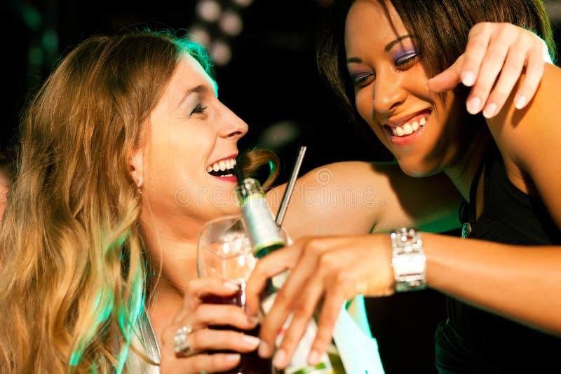 Amigos que tienen bebidas en barra o club fotografía de archivo libre de regalías