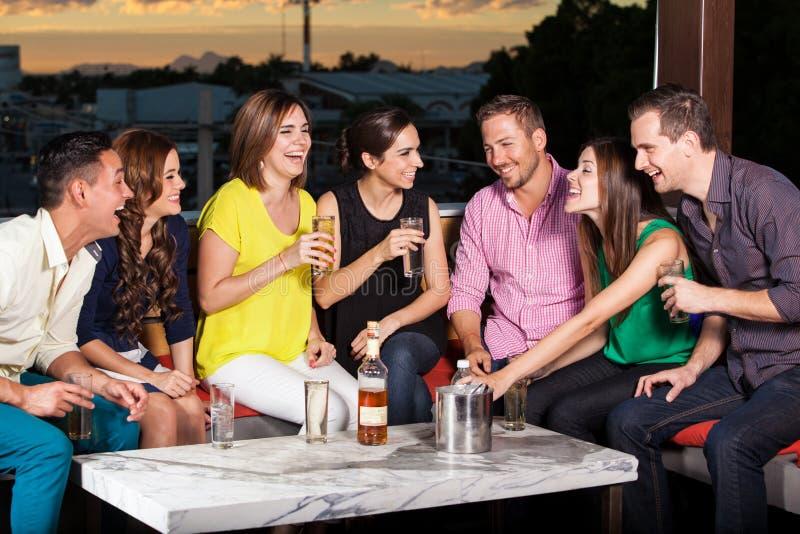 Amigos que tienen bebidas en la puesta del sol imagen de archivo libre de regalías