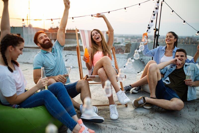Amigos que tienen partido encima del tejado Diversi?n, verano, forma de vida de la ciudad y concepto de la amistad imágenes de archivo libres de regalías