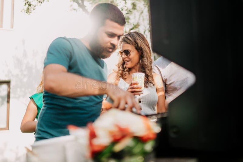 Amigos que tienen un partido de la parrilla de la barbacoa con las bebidas, la comida y cocinar al aire libre imagen de archivo