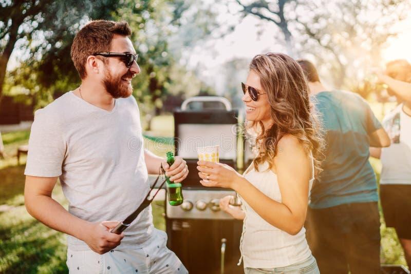 Amigos que tienen un partido de la parrilla de la barbacoa con las bebidas, la comida y cocinar al aire libre en naturaleza imágenes de archivo libres de regalías