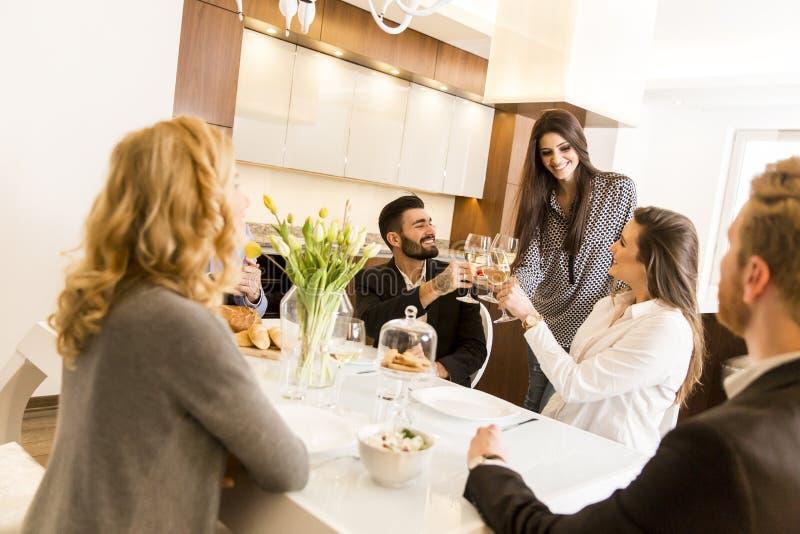 Amigos que tienen una comida en la mesa de comedor imagen de archivo libre de regalías