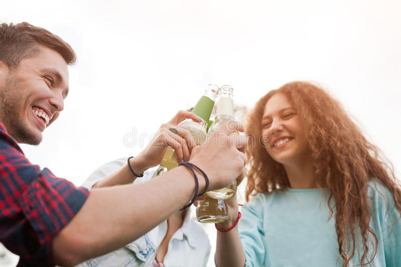 Amigos que tintinean las botellas de cerveza fotos de archivo libres de regalías