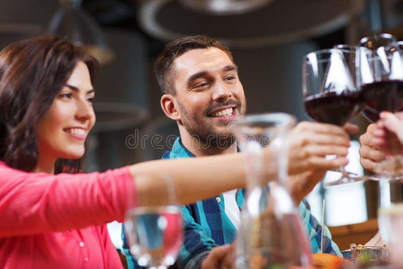 Amigos que tintinean los vidrios de vino en el restaurante fotografía de archivo