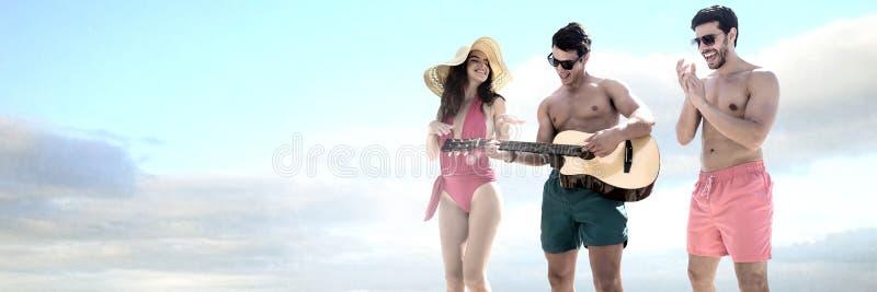 Amigos que tocan la guitarra y que se divierten en día de fiesta del desgaste de la nadada foto de archivo