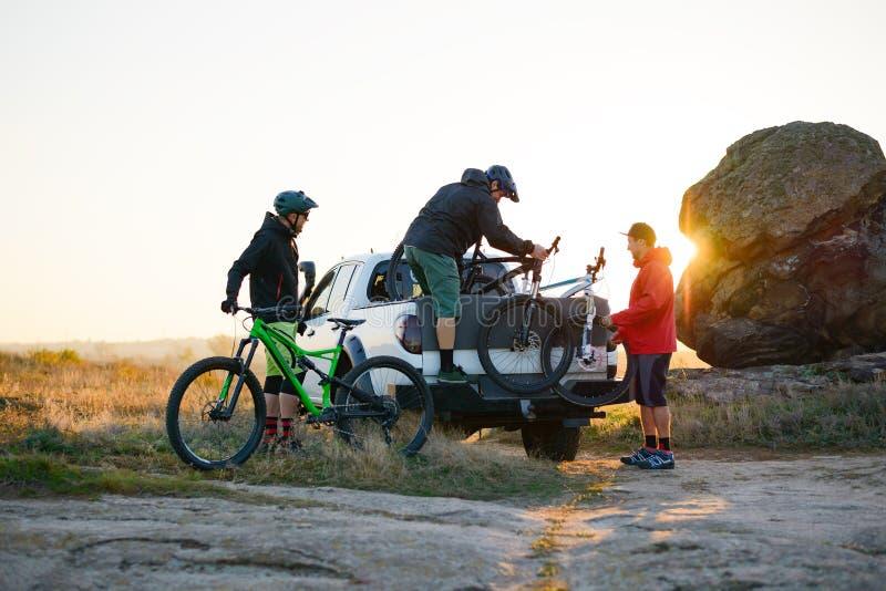 Amigos que tomam bicicletas de MTB fora do caminhão Offroad do recolhimento nas montanhas no por do sol Conceito da aventura e do fotografia de stock royalty free