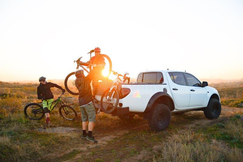 Amigos que tomam bicicletas de MTB fora do caminhão Offroad do recolhimento nas montanhas no por do sol Conceito da aventura e do fotos de stock royalty free