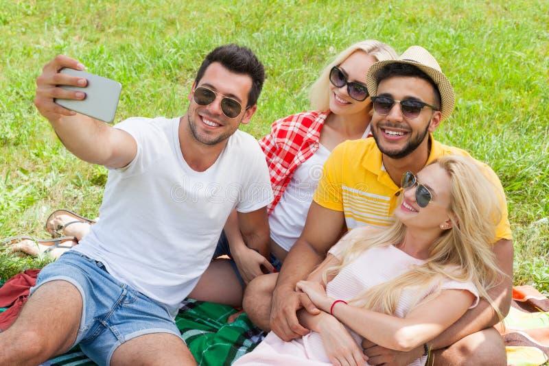 Amigos que tomam a foto do selfie o campo esperto do piquenique do telefone jovens imagem de stock