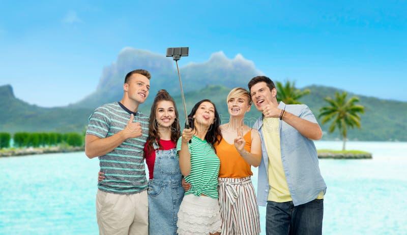 Amigos que tomam o selfie pelo smartphone sobre o bora do bora foto de stock
