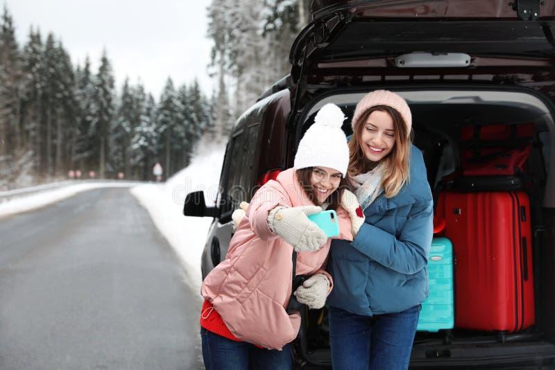 Amigos que tomam o selfie perto do tronco de carro aberto completamente da bagagem na estrada, espaço para o texto foto de stock royalty free