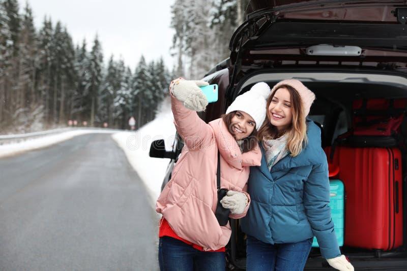 Amigos que tomam o selfie perto do tronco de carro aberto completamente da bagagem na estrada, espaço para o texto fotografia de stock