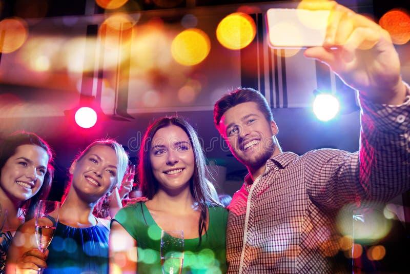 Amigos que toman el selfie por smartphone en club de noche fotografía de archivo