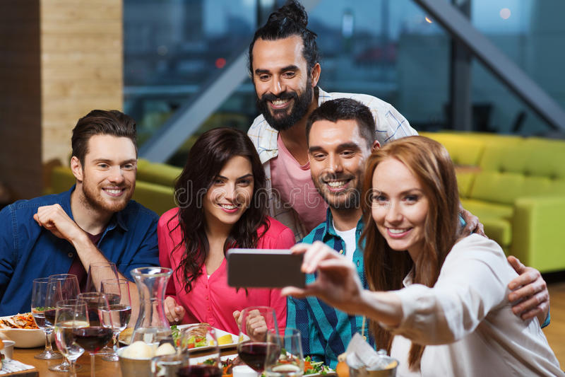 Amigos que toman el selfie por smartphone en el restaurante fotografía de archivo