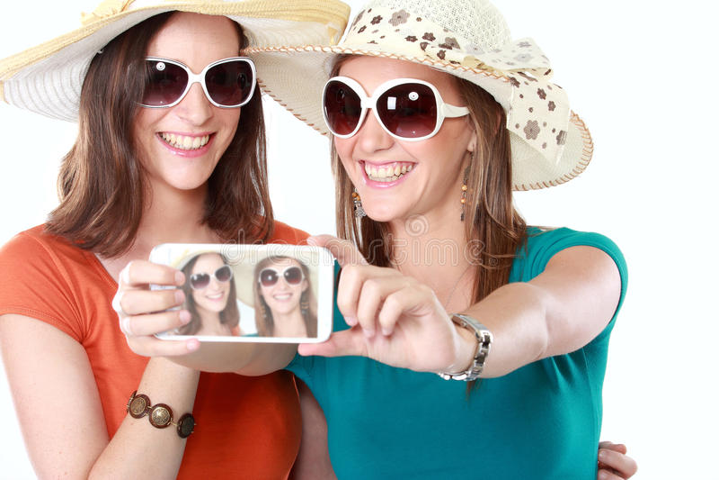 Amigos que toman las fotos con un smartphone imagenes de archivo
