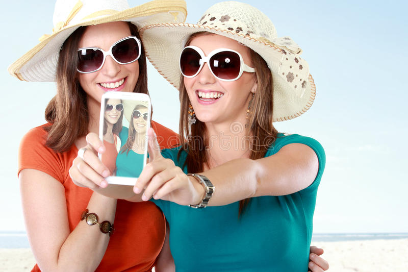 Amigos que toman las fotos con un smartphone imagen de archivo