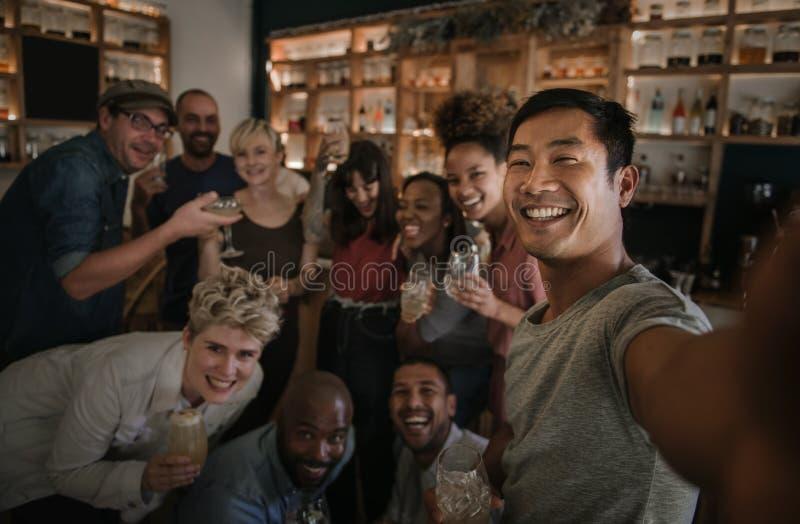 Amigos que toman selfies mientras que divirtiéndose en una barra foto de archivo