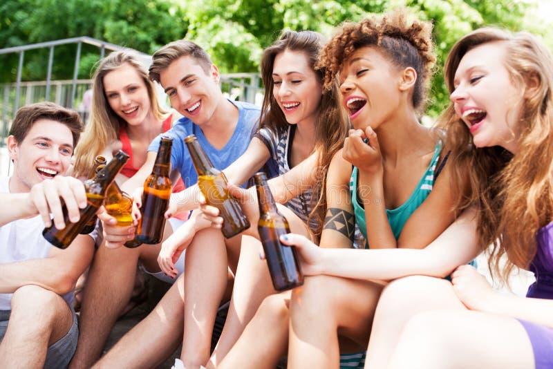 Amigos que tuestan con la cerveza imagenes de archivo